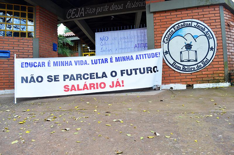 Em frente ao CEJA, faixa e cartaz externaram o protesto contra o parcelamento de salários. (Foto: Juliano Beppler da Silva / Giro do Vale)
